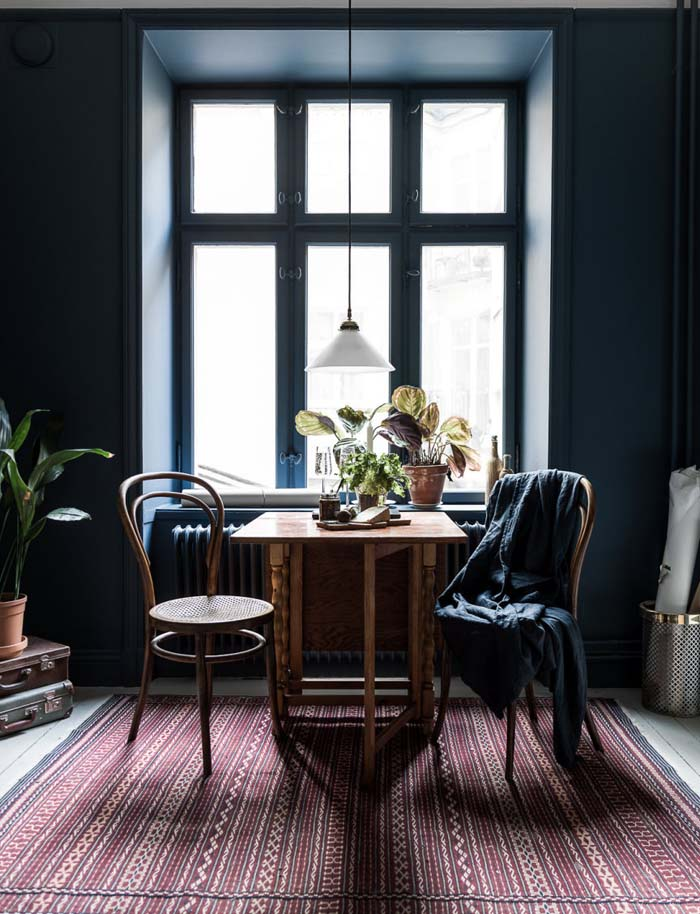 Dining Table Near Window With Dark Blue Wall